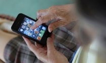 An-elderly-old-woman-uses-iphone